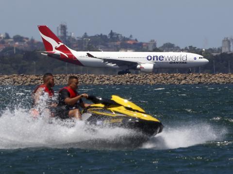 Un avión de Qantas se prepara para despegar de Sídney mientras pasa por delante una moto de agua