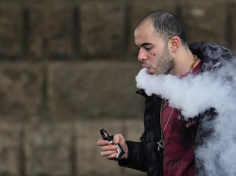 Chico joven vapeando un cigarrillo electrónico
