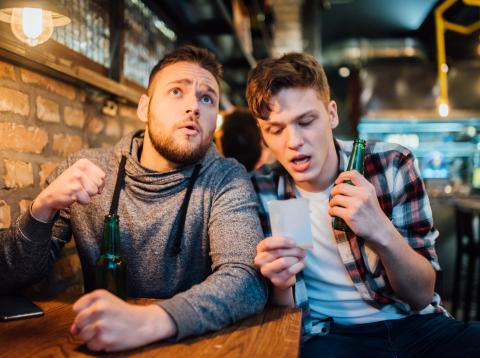 Dos jóvenes realizan una apuesta deportiva en un bar.