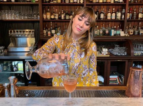 Camarera sirviendo una copa en un bar