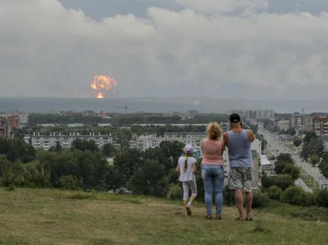 A family watches explosions at a military ammunition depot near Achinsk, Russia, on August 5. Russian officials say powerful explosions at the depot left 12 people injured and one missing and forced over 16,500 people to leave