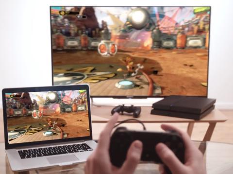 Jugador jugando a PlayStation 4 en televisión y ordenador Mac