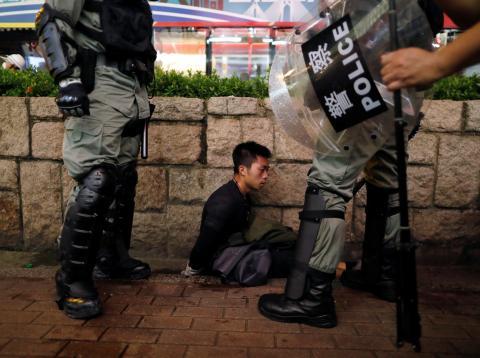 Policías antidisturbios detienen a un manifestante en el barrio de Tsim Sha Tsui, en Hong Kong.