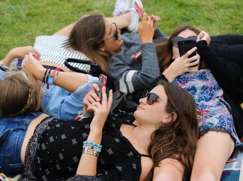 Grupo de jóvenes en el césped utilizando el móvil