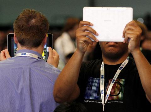 Dos hombres escondiéndose detrás de una tablet