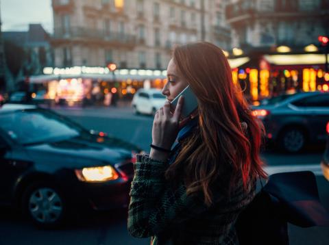 Mujer hablando por teléfono mientras anda por la calle