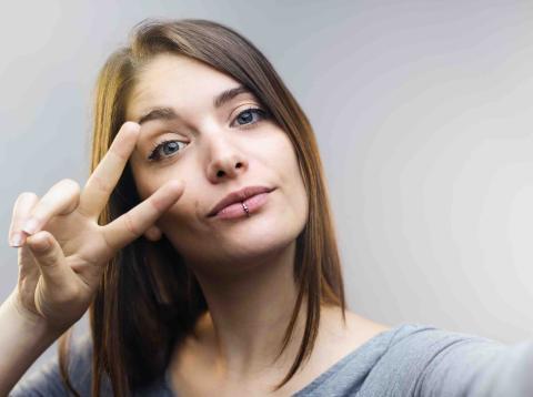 Una mujer se toma una foto haciendo el signo de la victoria.