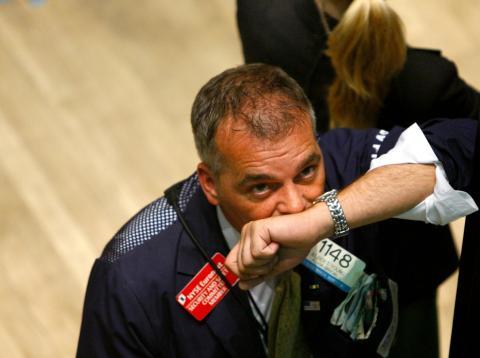 Un trader mira preocupado las pantallas de la bolsa