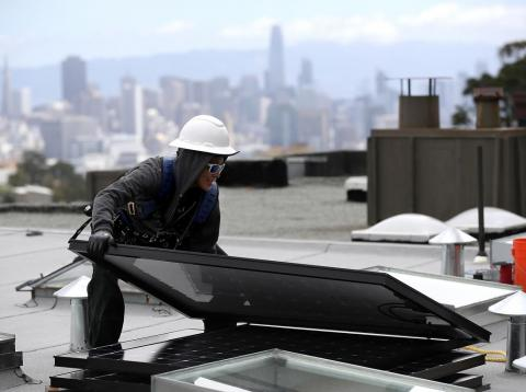 A woman moves a solar panel during an installation on a roof in San Francisco, California.