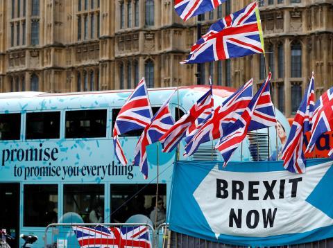 Una pancarta y varias banderas británicas en una calle de Londres