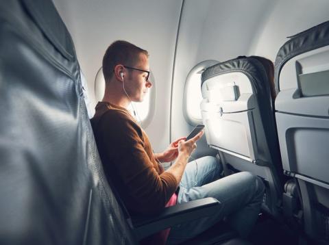 Chico usando el móvil en el avión