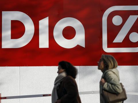 Mujeres pasando por delante de un supermercado Dia