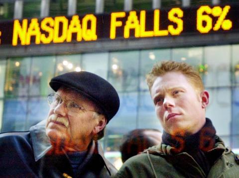 Dos inversores miran las pantallas de la bolsa de Nueva York durante el estallido de las puntocom