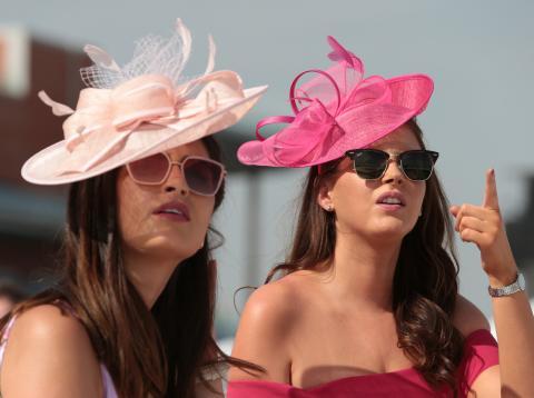 Dos mujeres jóvenes con pamela para un evento de gala