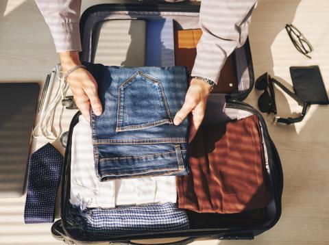 Hombre guardando ropa en la maleta