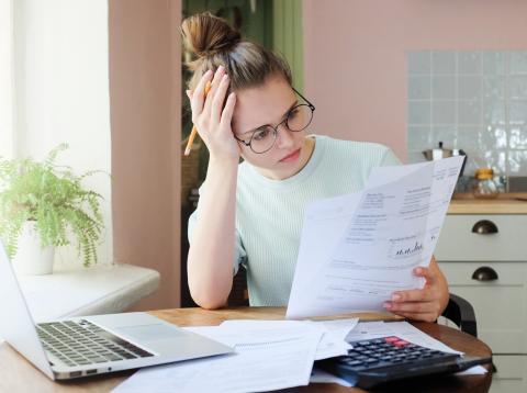 Una mujer repasa sus facturas y sus cuentas