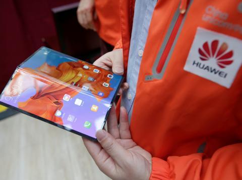 Un empleado muestra el Mate X plegable de Huawei