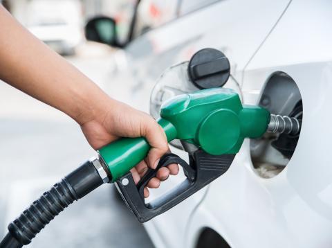Una mujer echando gasolina en un coche