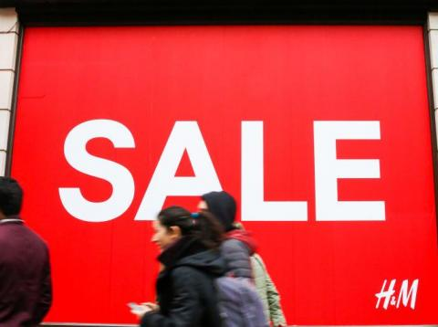 Shoppers are seen walking past H&M window display with a large SALE sign. Last minute Christmas shoppers take advantage of pre-Christmas bargains at Oxford Street in London. Fewer shoppers have been reported shopping in Britain's