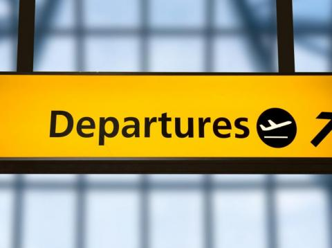 A sign for departures at Gatwick Airport, UK.