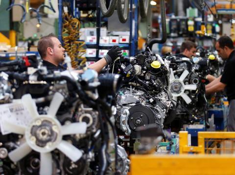 Trabajadores de Opel en una cadena de montaje de piezas de automóviles