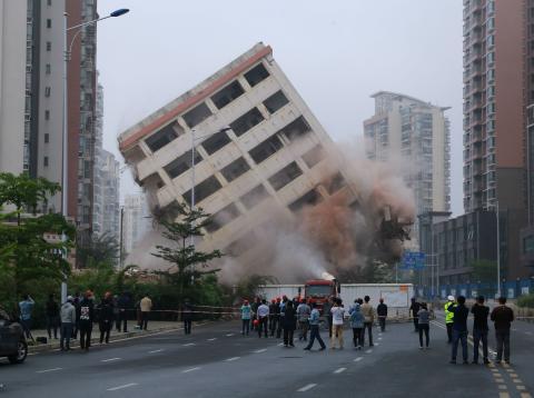 Varias personas observan la voladura controlada de un edificio en China.