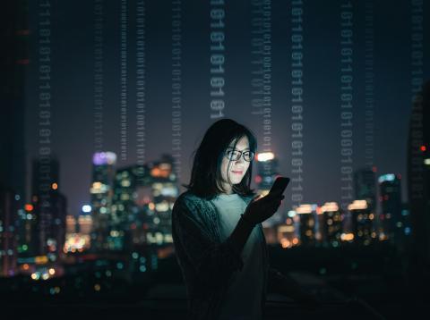 Chica con un móvil y un código de 0 y 1.