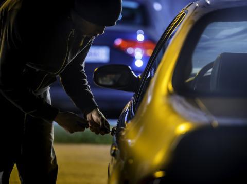 Un hombre robando un coche.