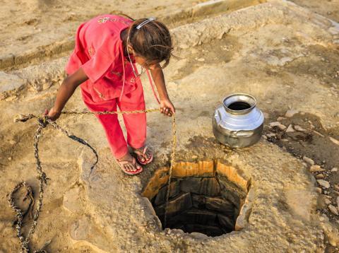 Niña tratando de extraer agua. Sequía del terreno