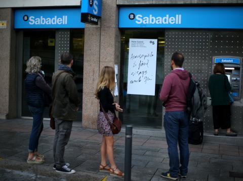 Un grupo de personas esperar en una cola ante un cajero automático en Barcelona