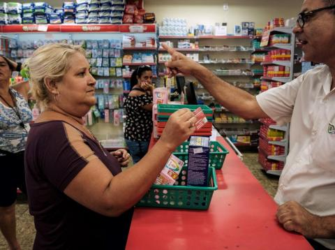 """A woman uses her """"mumbuca"""" card at a pharmacy in Marica, Brazil."""