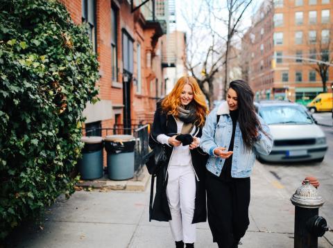 Un par de chicas pasea por la calle revisando el dinero que tiene en el monedero