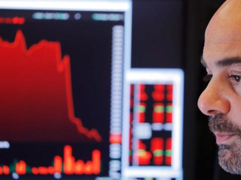 Un inversor observa el movimiento de la bolsa en las pantallas de Wall Street