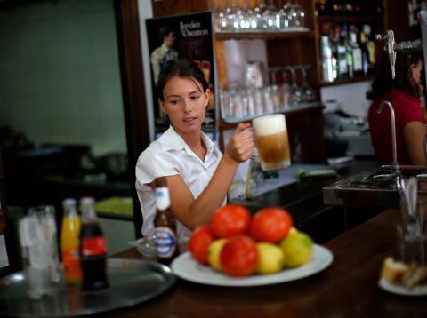 Una camarera sirve una cerveza en un bar de Ronda (Málaga)