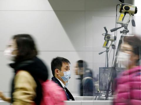 Passengers wearing masks walk by as a quarantine officer, center, monitors a thermography during a quarantine inspection at Kansai international airport in Osaka, western Japan, Wednesday, Jan. 22, 2020. Chinese health authorities