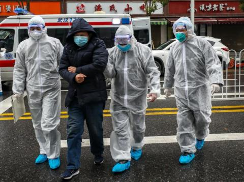 Medics help a patient walk into a hospital in Wuhan, China, on January 26, 2020.