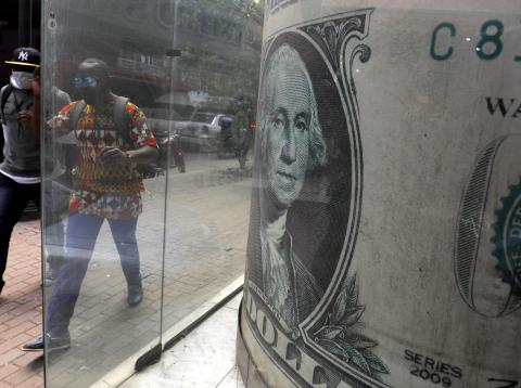 Dos personas pasan al lado de un billete de un dólar.
