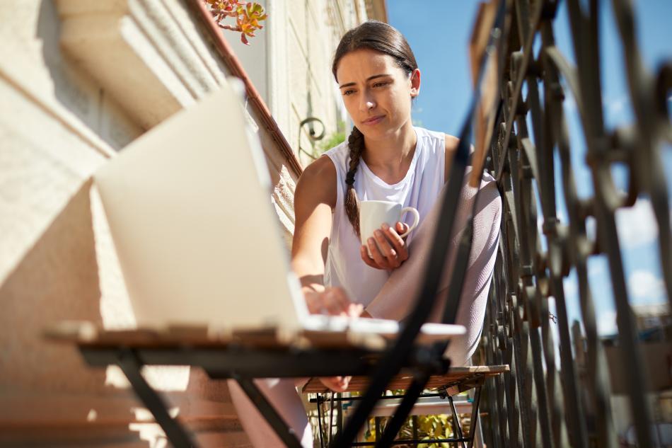 Una mujer joven con una taza de café en un balcón con un ordenador portátil