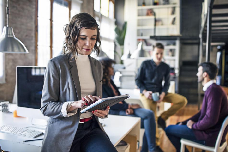 Una mujer en una oficina trabajando con una tablet