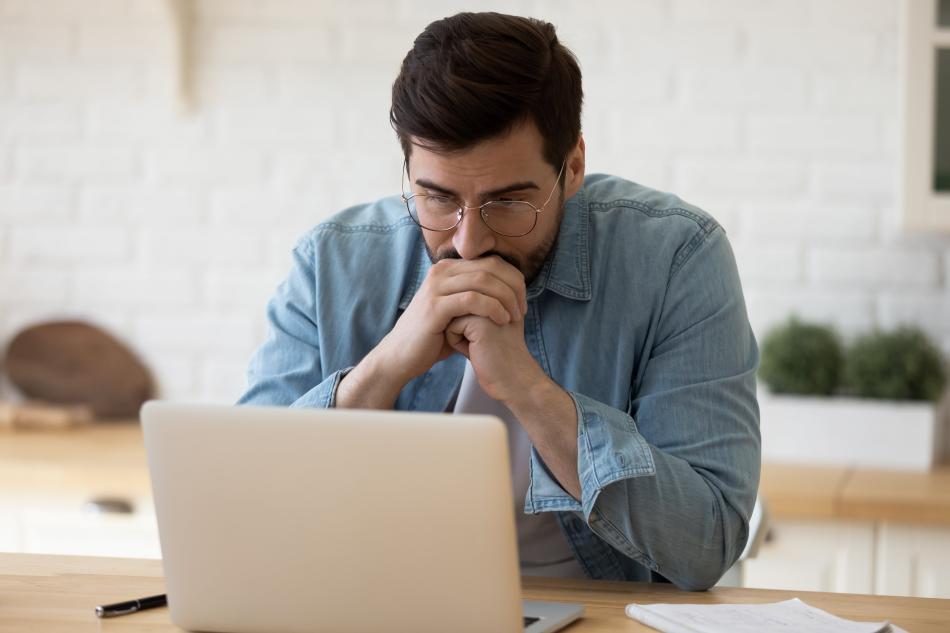 Hombre mira preocupado su ordenador