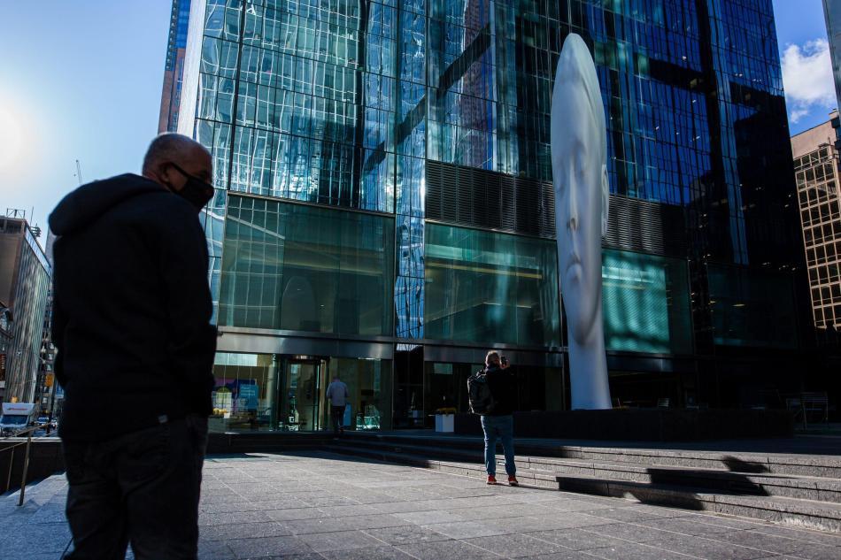 La gente pasa junto a esta ilusión óptica titulada 'Dreaming' del artista español Jaume Plensa.