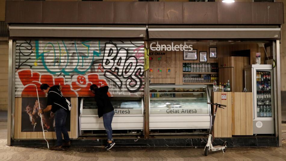 2 empleados de una tienda de helados de Barcelona echan el cierre antes del toque de queda