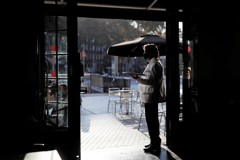 Un camarero en la puerta de un bar en Barcelona durante la pandemia de COVID-19.