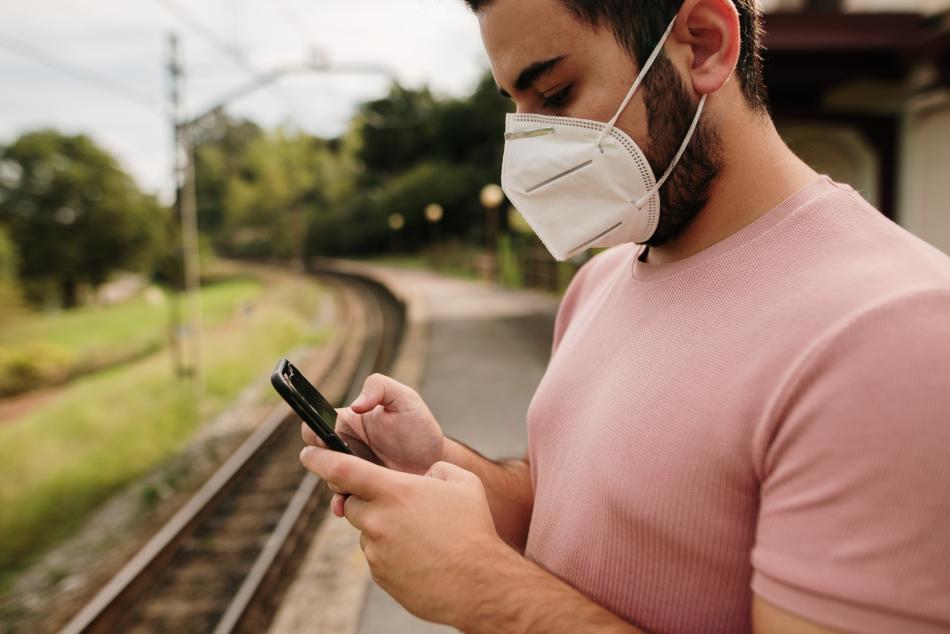 Persona llevando mascarilla FFP2 sin válvula mientras espera al tren