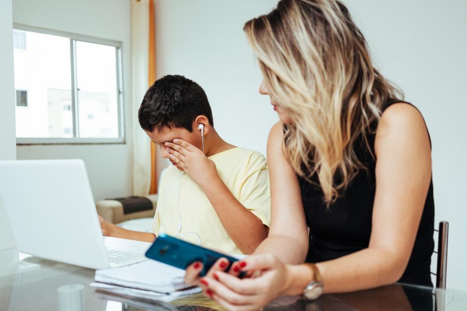 Una madre trata de ayudar a su hijo (que está llorando) a hacer los deberes