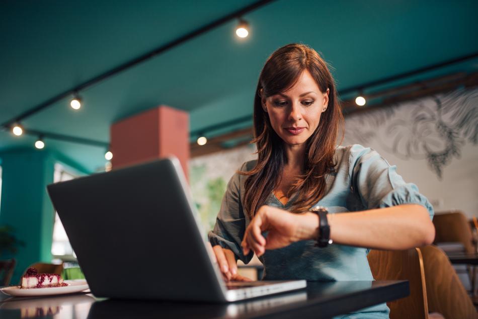 Una mujer mira el reloj mientras trabaja en el ordenador.