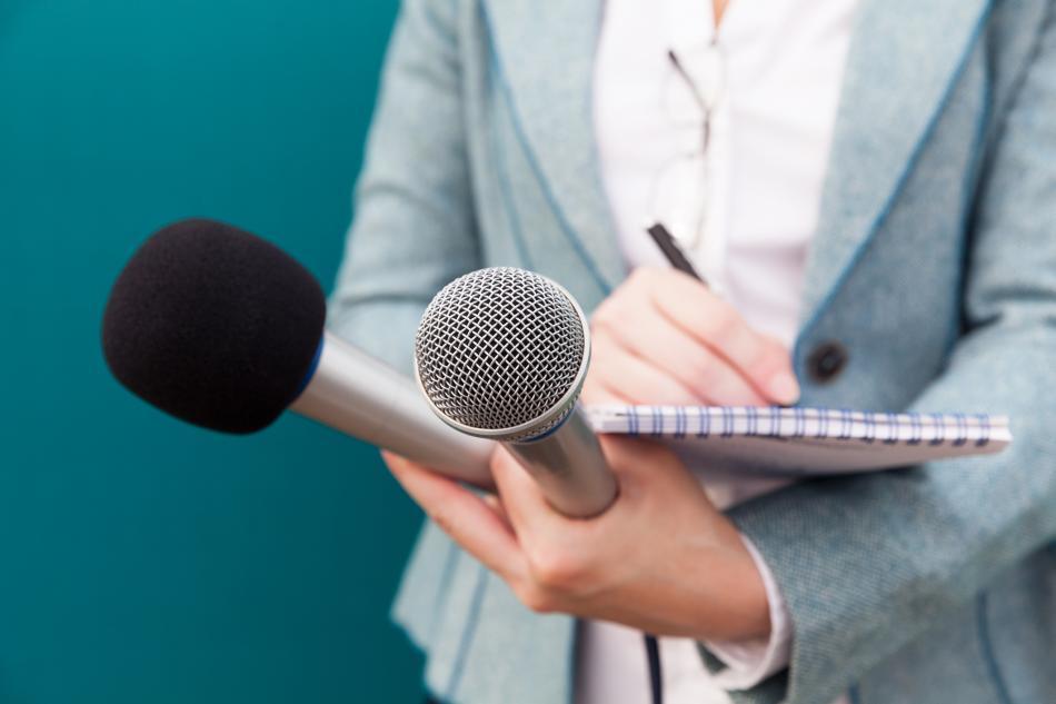 Una persona anota algo en un cuaderno, mientras sostiene dos micrófonos.