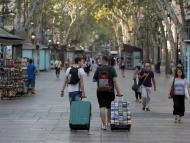 Unos turistas pasean por Las Ramblas de Barcelona.