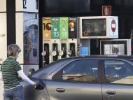 Una mujer repostando su coche en una gasolinera