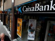 Un hombre pasa junto a una sucursal de CaixaBank en Barcelona